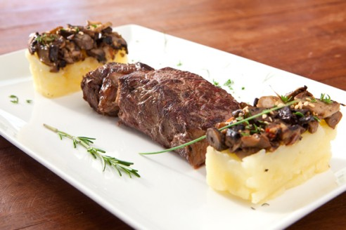 Bife ancho com purê de palmito pupunha trufado e cogumelos frescos salteados.