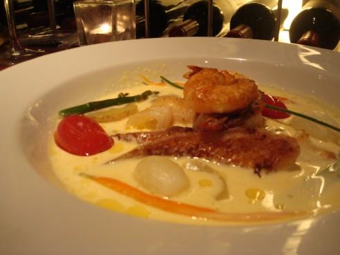 Nage de frutos do mar - lula, camarão, lagosta e peixe em seu caldo com açafrão e legumes acompanhados de arroz de limão